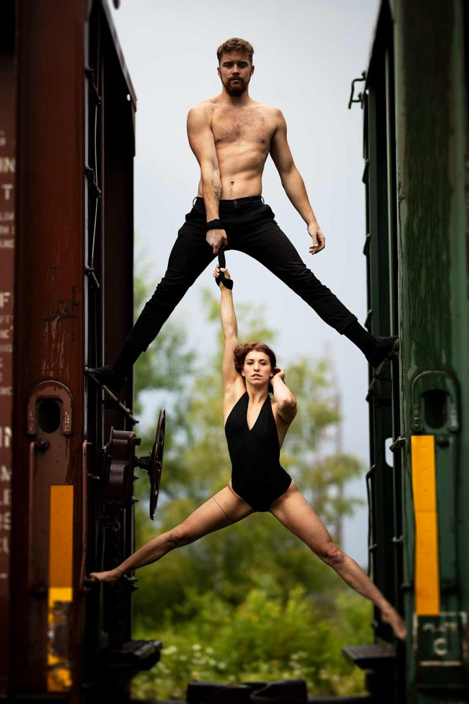 Circus artists between two train cars