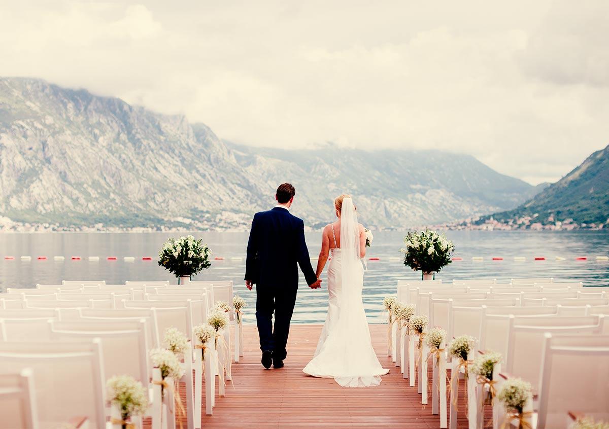 back of wedding couple facing a mountain range and lake