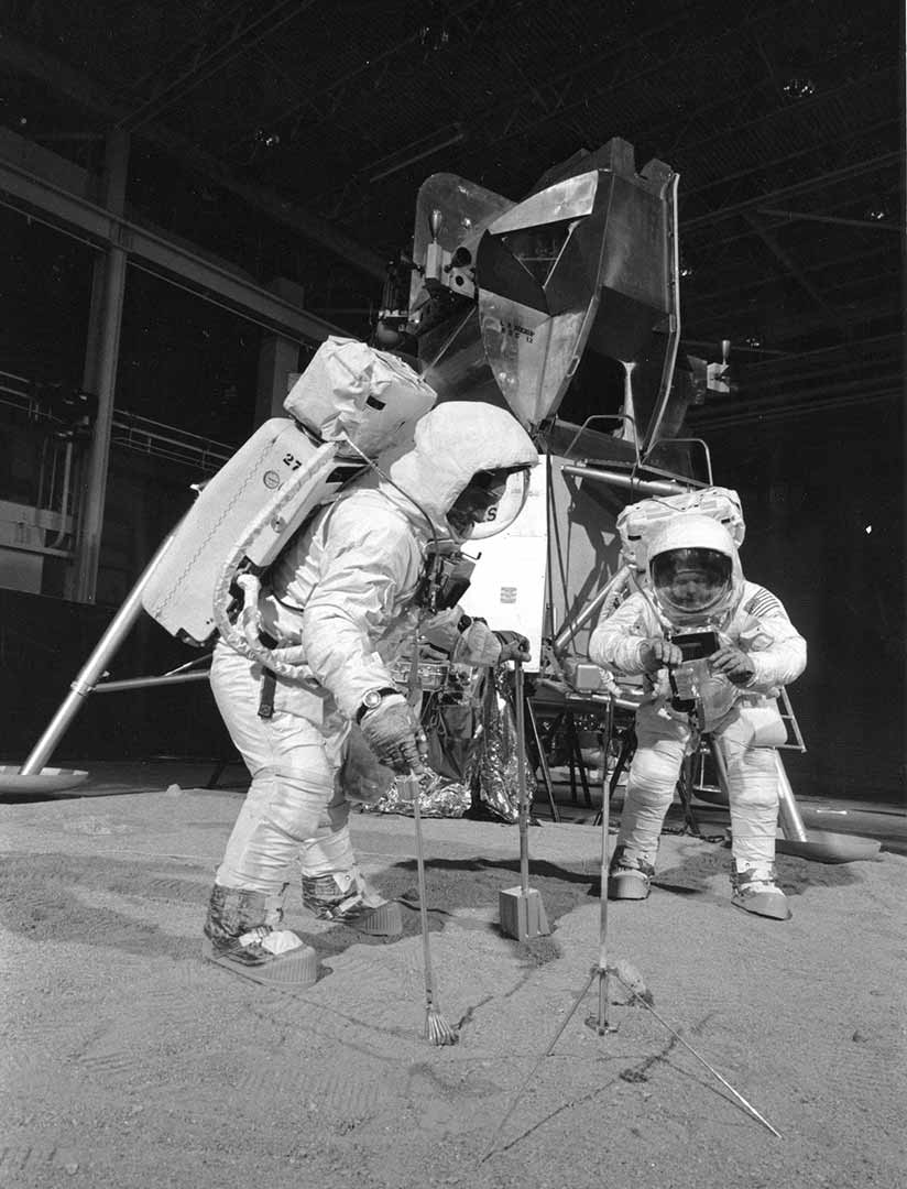 Neil Armstrong and Buzz Aldrin in spacesuits on a mockup of the moon